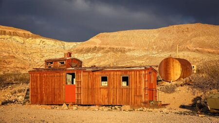 railway transport: An abandoned red caboose in warm light in the ghost town of Rhyolite near Death Valley National Park