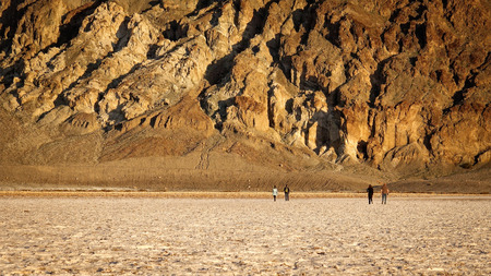 valley below: Tourists walk on the salt flats in Badwater Basin in Death Valley National Park.