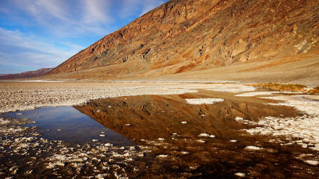 valley below: A small pool of water in Badwater Basin in Death Valley National Park. Badwater Basin in the lowest point in North America at 282 feet below sea level.