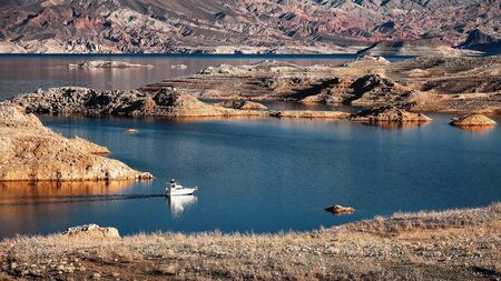 mead: A white motorboat cruising through a channel in Lake Mead