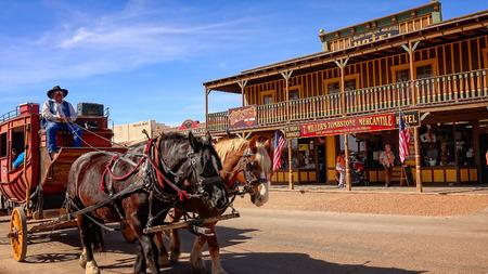 Stagecoach piena di turisti rotola giù per le vie del paese selvaggio west di Tombstone, Arizona Archivio Fotografico - 55062000