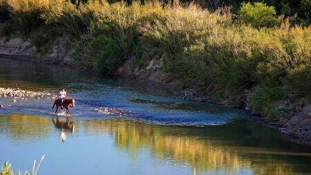 Mexikanischer Mann auf einem Pferd reitet durch den Rio Grande Fluss Big Bend Nationalpark Standard-Bild - 55765700