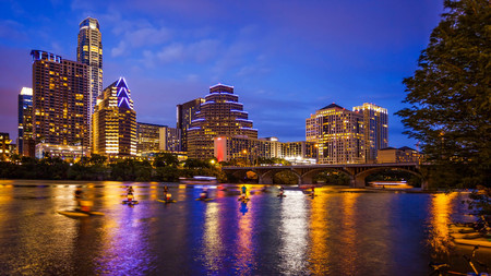 Austin, Texas downtown skyline at night on the Colorado River as unidentified tourists ride water bikes (All recognizable faces, building names and signs have been blurred for commercial use) Stock Photo