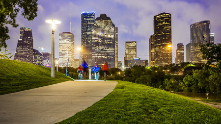 Houston city skyline as night falls and people enjoying Eleanor Tinsley Park