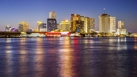 Downtown New Orleans skyline across the Mississippi River as night falls (Building logos blurred for commercial use)