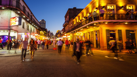 Bourbon Street in the French Quarter of New Orleans as night falls and the lights come on