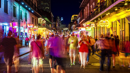 People enjoying famous Bourbon Street at night in the French Quarter of New Orleans, Louisiana Editorial
