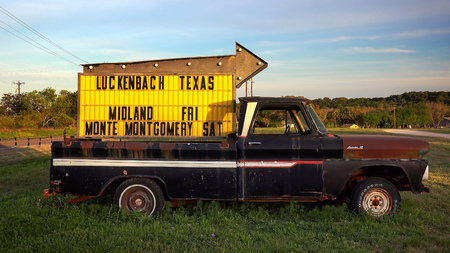 Sign on a pickup truck points the way to Luckenbach, Texas