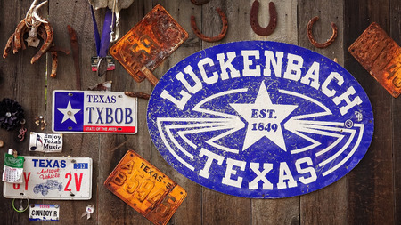 Luckenbach, Texas sign and memorabilia on the side of a wooden barn