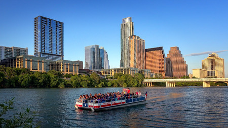 Austin, Texas skyline and tour boat packed with tourist on the Colorado River