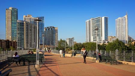 Pedestrians walk over pedestrian bridge to downtown Austin, Texas