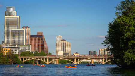 Austin, Texas skyline during the day with kayakers enjoying the Colorado River