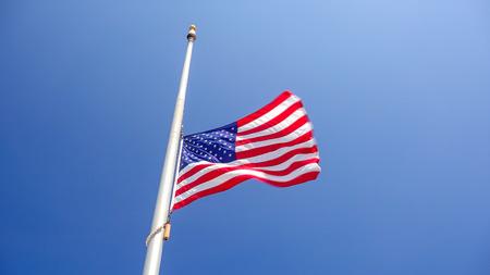 American flag flying at half mast aka half staff against a clear blue sky