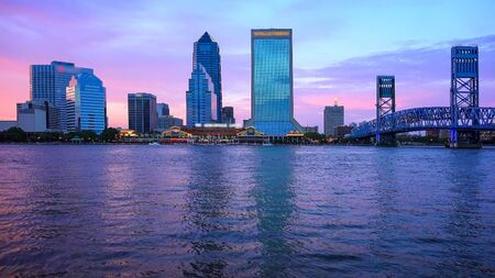 Jacksonville, Florida city skyline over the St. Johns River at sunset (logos blurred for commercial use)