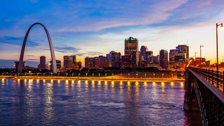 El horizonte del paisaje urbano de San Luis, Missouri y Gateway Arch, mientras cae la noche sobre el centro de la ciudad (los logotipos se eliminan para uso comercial)