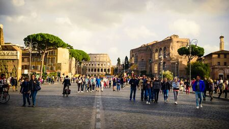 Tourists walk along Via dei Fori Imperiali at the Roman Forum with the Colosseum in background