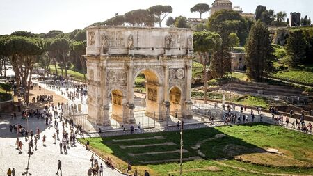 Arch of Constantine surrounded by tourists in Rome, Italy