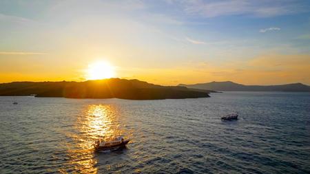 Ships cruise near uninhabited volcanic greek islands at sunset in the Mediterranean near Santorini, Greece