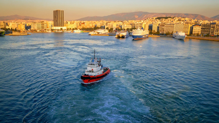Port of Piraeus and Athens, Greece skyline. The largest Greek seaport, ship logos removed or blurred for commercial use