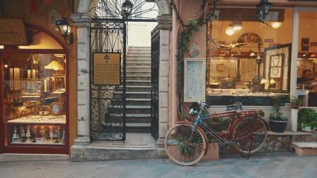 Bike and shops on a narrow street in Old Town, Corfu, Greece