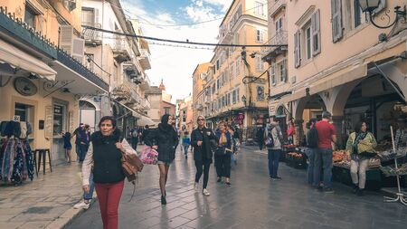People walking and shopping on a street in old town Corfu, Greece