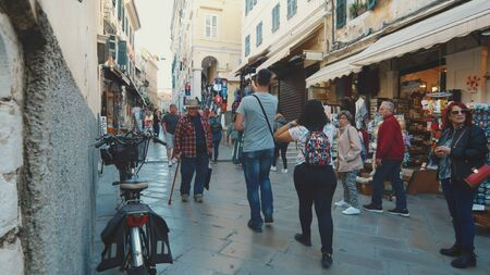 People shopping on a narrow street in old town Corfu, Greece