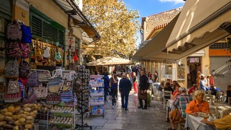 Tourists shopping and enjoying outdoor cafe in the famous Plaka neighborhood in Athens, Greece