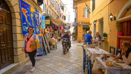 People shopping and eating on a narrow street in old town Corfu, Greece Editoriali