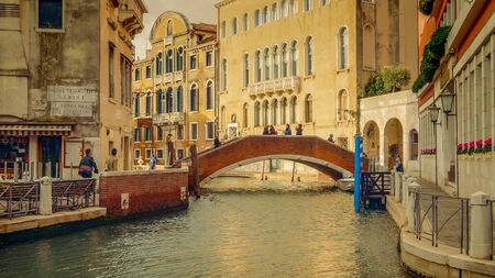 Picturesque brick bridge over small, quiet canal off of the Grand Canal in Venice, Italy