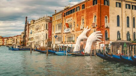 The Giant Hands sculpture by Lorenzo Quinn appears to hold up a building along the Grand Canal in Venice, Italy The support shows concern for the effects of climate change