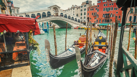 Empty gondolas in front of Rialto Bridge. The bridge is a famous international landmark in Venice, Italy Archivio Fotografico