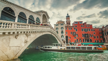 Vaporetto passes underneath Rialto Bridge. The bridge is oldest bridge crossing the Grand Canal  in Venice, Italy Archivio Fotografico