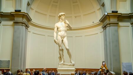 Statue of David by Michelangelo surrounded by tourists in Florence, Italy