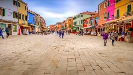 Tourists visiting shops in the picturesque fishing village of Burano in Venice, Italy