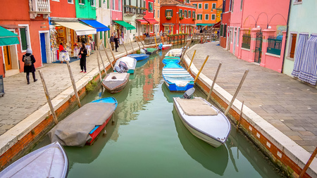 A canal runs through the colorful fishing village of Burano in Venice, Italy