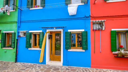 Front doors of brightly painted fishermans houses on the island of Burano in Venice, Italy