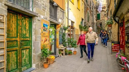 CORNIGLIA, ITALY - NOVEMBER 14th: Tourists walk along a narrow alley in the Cinque Terre village of Corniglia  in the province of La Spezia on November 14th, 2017