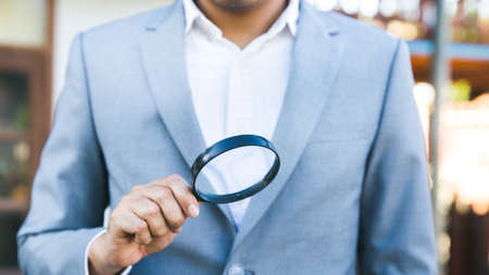 Businessman in grey suit looking through a magnifying glass to contract.