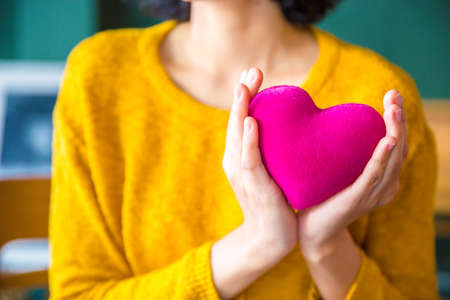 people, age, family, love, valentine and health care concept - close up of  woman  hands in yellow sweather holding pink heart.