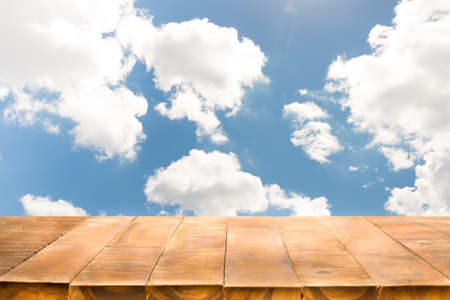 Empty of wooden table with perspective and bright cloudy sky in the morning. Stock Photo