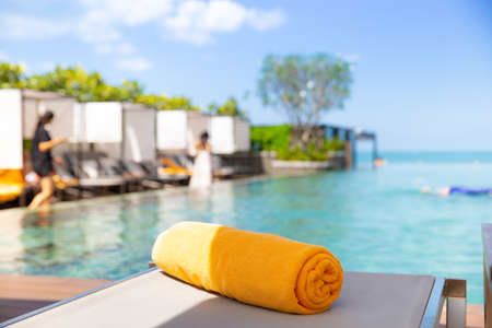 Yellow towel on the bed cushion by the infinity swimming pool.