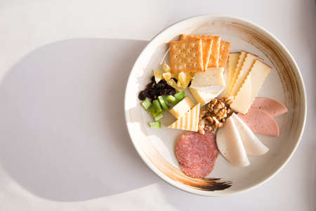 Cheese platter with different cheese, crakers, ham, nuts, salami, avocado and rum raisins. Breakfast with white background copy space. Top view. Archivio Fotografico