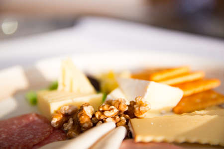 Close up of Cheese platter with different cheese, crakers, ham, nuts, salami, avocado and rum raisins. Archivio Fotografico