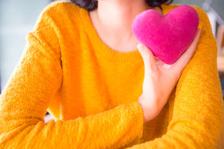 Romantic young asian woman with pink heart-shaped pillow and gifts for Valentine's Day. Stok Fotoğraf