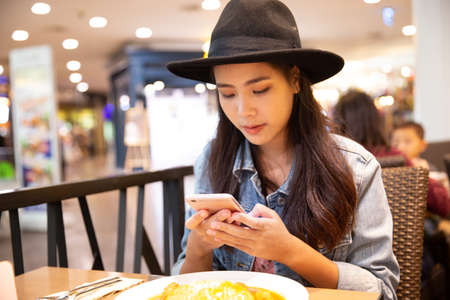 Young hipster asian woman wearing a black hat using her smartphone in the restaurant. Stockfoto