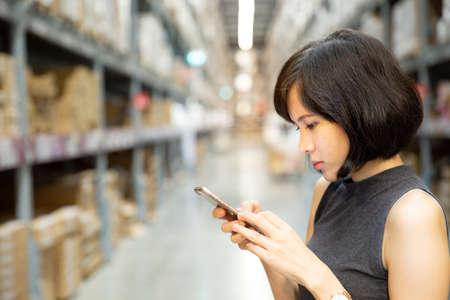 Une belle femme utilisant un téléphone intelligent à l'entrepôt, une recherche ou un concept de réseaux sociaux, une femme hipster tapant un message sms. Banque d'images