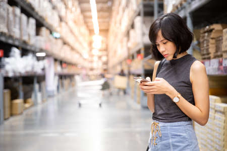 An asian woman doing shopping online via mobile phone in the warehouse. Cart and boxes on rows of shelves in warm light warehouse background.  Using for Mock up template for craft display of your design,Banner for advertise of product. Standard-Bild