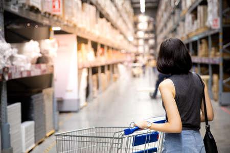 Eine asiatische Frau, die einkaufen und mit ihrem Wagen in Fracht oder Lagerhaus geht. Boxen auf Reihen von Regalen in warmem hellem Hintergrund. Speicherplatz kopieren