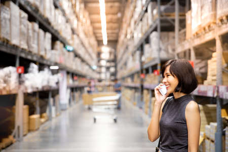 An asian businesswoman having a phone conversation in the warehouse. Cart and boxes on rows of shelves in warm light warehouse background.  shopping concept. Stockfoto