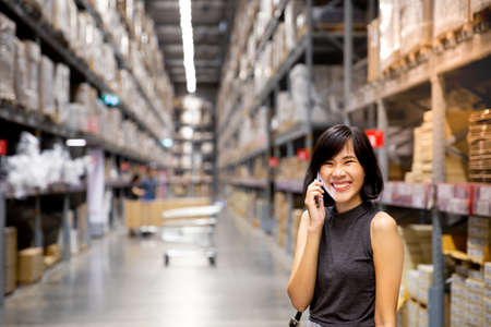An asian woman doing shopping online via mobile phone in the warehouse. Cart and boxes on rows of shelves in warm light background. copy space